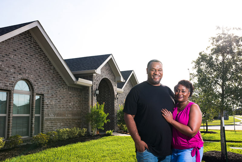 Smiling man and woman in front yard on summer day