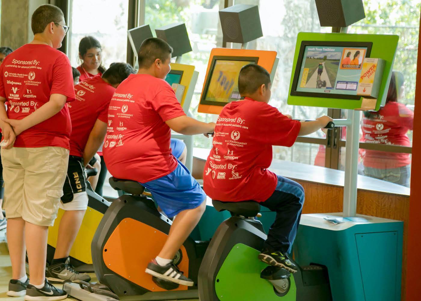 Children riding stationery bike
