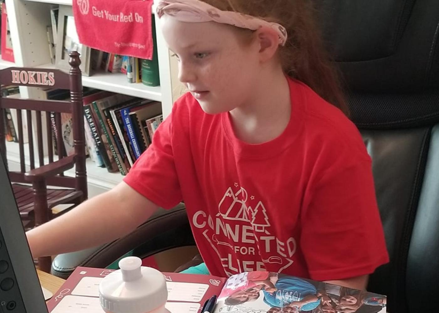 Girl in red shirt and pink bandanna at computer