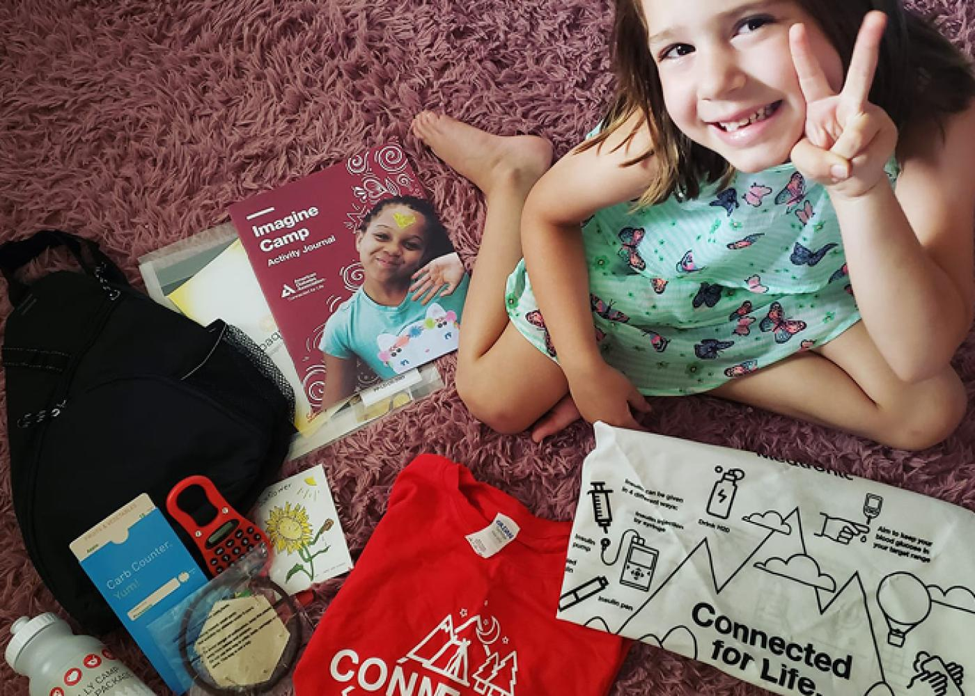 Girl in green dress on pink shag carpet with camp materials giving peace sign surrounded by camp swag