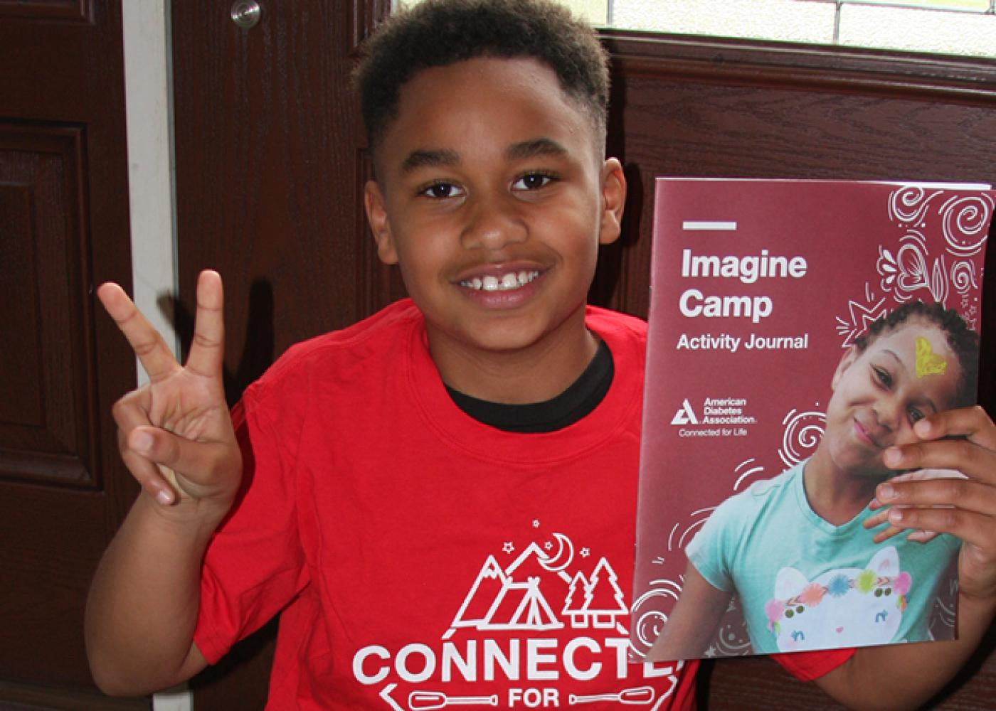 Happy African American kid flashing peace sign and holding up activity journal