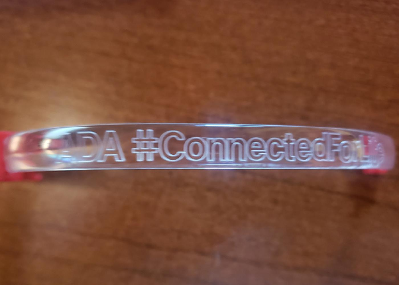 Close-up of ADA#Connected acrylic wrist band