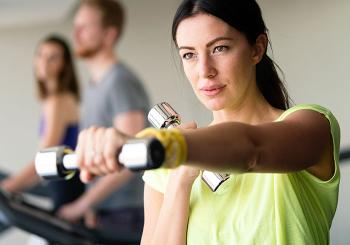 young in woman green shirt exercising with chrome dumbbells