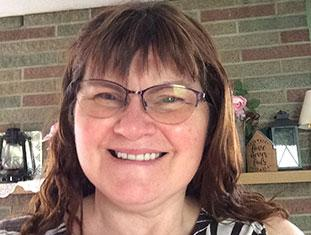 Lori Willey smiling wearing glasses