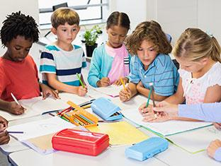 Mixed group of children at table with teacher going over lesson
