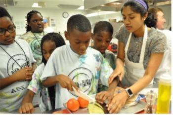 Children in kitchen cutting up produce
