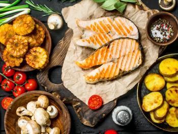 grilled salmon on cutting board surrounded by grilled corn, mushrooms, tomatoes, grilled zucchini, wooden bowl with peppercorns and salt