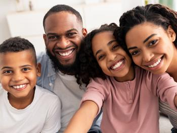 Happy African American family of son, father, daughter, and mother smiling.