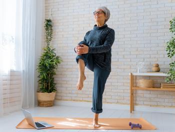 senior woman standing on yoga mat and lifting leg