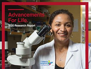 smiling researcher with microscope on cover of 2020 research report