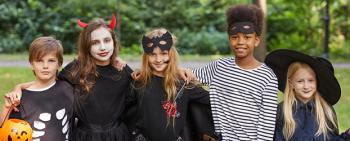 Group of five pre-teenage boys and girls dressed in halloween costumes